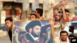 ພວກທະຫານບ້ານ Mahdi Army ຍໍຮູບພາບນັກບວດຫົວຮຸນແຮງ Muqtada al-Sadr ຂອງອິຣັກ.