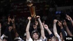 Los Mavericks de Dallas celebran su primer campeonato de la NBA, con Dirk Nowitzki, el jugador más valioso, levantando el trofeo de campeón.