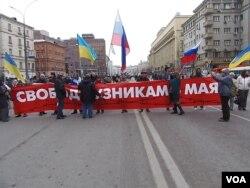 2014年3月在莫斯科举行的一场反对侵略乌克兰的抗议集会上,示威者手举乌克兰和俄罗斯国旗,呼吁释放政治犯。