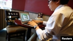FILE - A man works on his computer inside a coffee shop in downtown Shanghai, Sept. 25, 2013.