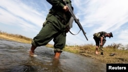 A soldier from the Kachin Independence Army (KIA) puts on his shoes as he and his comrade cross a stream towards the front line in Laiza, Kachin state, January 29, 2013.