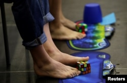 Competitors solve Rubik's cubes using their feet during the Rubik's Cube European Championship in Prague, July 2016.