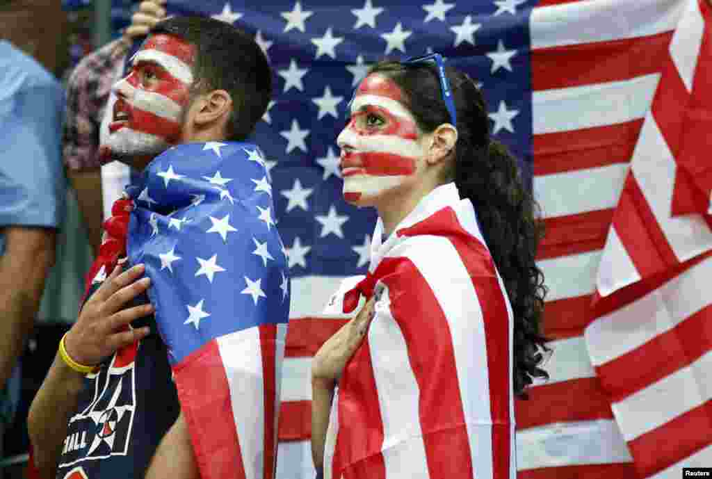 Fans of the U.S. Jamie (L) and Allison Zaslav wait for the start of the men's preliminary round Group A basketball match against Lithuania at the Basketball Arena during the London 2012 Olympic Games August 4, 2012.