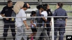 Ever Castillo y su familia, inmigrantes de Honduras, son escoltados de regreso a la frontera por agentes de la Patrulla de Aduanas y Fronteras de los EE.UU., el 21 de junio de 2018, en Hildalgo, Texas.