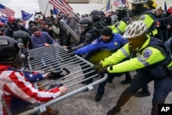 FILE - In this Jan. 6, 2021, photo, rioters try to break through a police barrier at the Capitol in Washington.