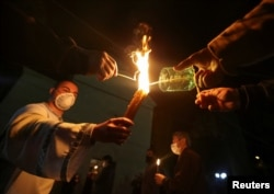 A clergyman and believers wearing protective masks hold candles outside a church during an Orthodox Easter service, amid the coronavirus disease outbreak in Marneuli, Georgia, April 19, 2020.