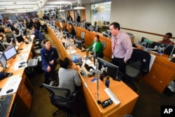 FILE - Personnel at the the Centers for Disease Control and Prevention work at the Emergency Operations Center in response to the 2019 novel coronavirus, Feb. 13, 2020, in Atlanta.
