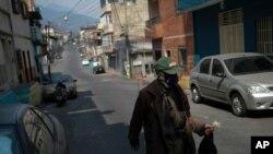 Hombre usa máscara protectora como precaución contra la propagación del coronavirus mientras camina en el barrio de Lidice de Caracas, Venezuela.