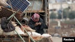 ຜູ້ຊາຍທີ່ເປັນອົບພະຍົບພາຍໃນປະເທດຄົນນຶ່ງ ທີ່ຫຼົບໜີຈາກແຂວງອິດລິບ ພວມຮຳຢາສູບ ຂະນະທີ່ລາວ ນັ່ງຢູ່ທາງຫຼັງ ລົດບັນທຸກ ພ້ອມເຄື່ອງຂອງ ທີ່ເມືອງອາຊາສ ເມື່ອວັນທີ 15 ກຸມພາ 2020. REUTERS/Khalil Ashawi