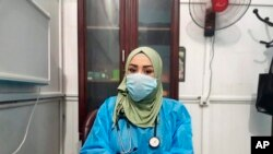 This May 13, 2020, picture provided by Dr. Marwa al-Khafaji shows the doctor back at work after 20 days in isolation after she tested positive for the coronavirus at a hospital in Karbala, Iraq.