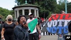 រូបឯកសារ៖ បាតុករម្នាក់ (ខាងមុខគេ) ស្រែកទទូចឲ្យអ្នកតវ៉ាផ្សេងឲ្យក្រោកឈរឡើង ដើម្បីក្លាយជាសកម្មជនក្នុងអំឡុងពេលជួបជុំនៃចលនា Black Lives Matter ដែលធ្វើឡើងនៅទីលាន Grand Army Plaza ក្នុងសង្កាត់ Brooklyn ទីក្រុងញូវយ៉ក។