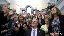 Massachusetts Governor Charlie Baker smiles as he signed a bill into law requiring men and women be paid equally for comparable work in Massachusetts. (AP Photo/Elise Amendola)