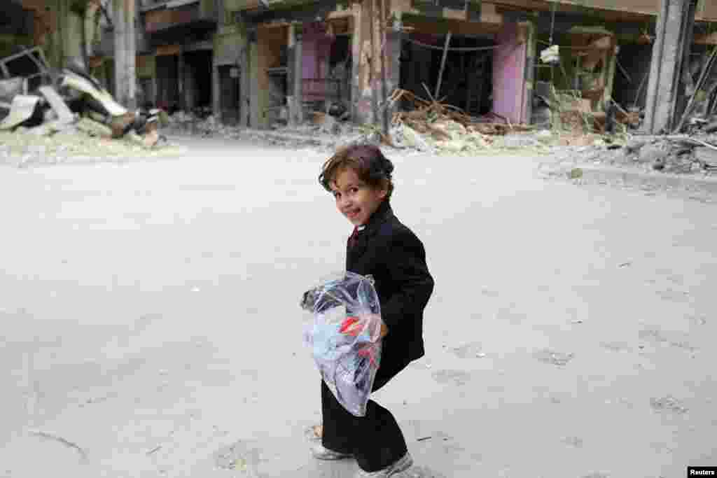 A boy carries a bag of new clothes ahead of the Eid al-Fitr holiday marking the end of Ramadan, in Jobar, a suburb of Damascus, Syria, July 15, 2015.