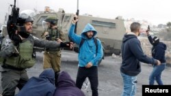 Un agent de sécurité israélienne détient des manifestants palestiniens