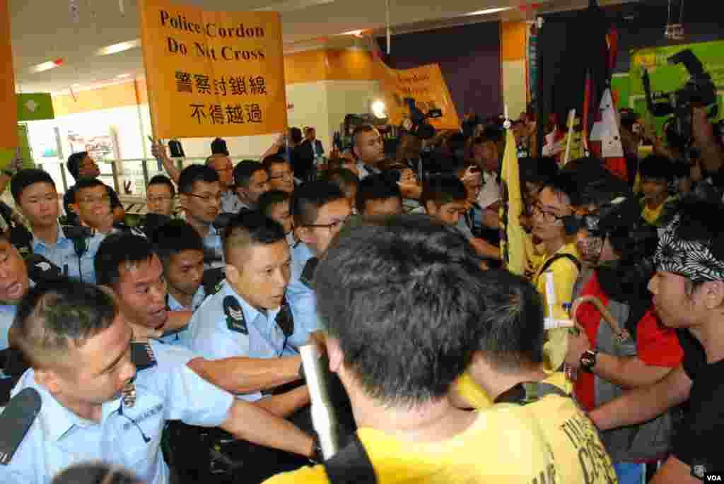 十多名熱血公民成員衝擊北京官員政改簡介會演講廳外的警方鐵馬陣,警方3度在室內施放胡椒噴霧,制止示威者衝擊