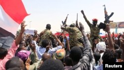 Sudanese military officers and demonstrators ride atop a military tanker as they protest against the army's announcement that President Omar al-Bashir would be replaced by a military-led transitional council, near Defense Ministry in Khartoum, Sudan, April 12, 2019.
