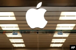 FILE - The Apple logo is seen above a store entrance, in Dallas, Sept. 19, 2013.