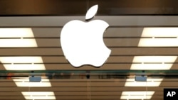 FILE - The Apple logo is seen above a store location entrance, in Dallas, Texas, Sept. 19, 2013.