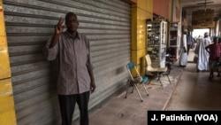Siddig Ibrahim menunjukkan tanda V (Victory) saat melancarkan aksi mogok dengan menutup tokonya di Khartoum, Sudan, Selasa (28/5).