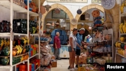 FILE - Russian tourists are seen shopping at the old medina in Sousse, Tunisia, Sept. 30, 2017.
