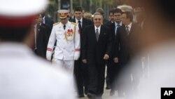 El presidente cubano Raúl Castro, centro, llega al mausoleo del líder comunista Ho Chi Minh, en Hanoi, Vietnam, el lunes 9 de julio de 2012.