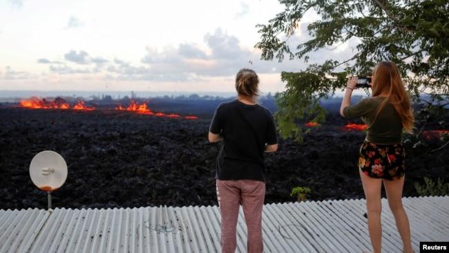 Jolon Clinton, (izquierda), y su hermana Halcy, toman fotos de una fisura del volcán Kilauea cerca de su casa en las afueras de Pahoa, Hawái, el lunes, 14 de mayo, de 2018.