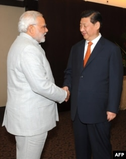 In this photograph received from the Press Information Bureau (PIB) and taken on July 14, 2014, Indian Prime Minister Narendra Modi (L) shakes hands with Chinese President Xi Jinping during the BRICS summit in Fortaleza, Brazil.