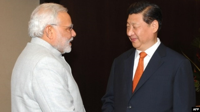 Indian Prime Minister Narendra Modi (L) shakes hands with Chinese President Xi Jinping during the BRICS summit in Fortaleza, Brazil, In this photograph received from the Press Information Bureau (PIB) and taken on July 14, 2014,
