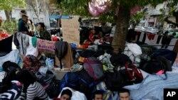 Des migrants reposent sous un arbre sur la Place Victoria à Athènes, en Grèce, le premier mars 2016. (AP Photo/Thanassis Stavrakis)