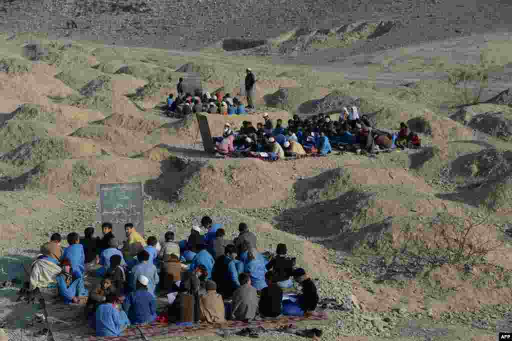 Afghan schoolchildren study at an open-air classroom in the Mohmand Dara district in eastern Nangarhar province.