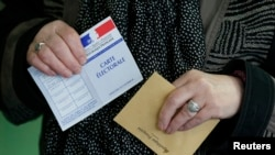 Seorang perempuan bersiap memberikan suara di TPS di Henin-Beaumont, Perancis utara (29/3). (Reuters/Pascal Rossignol)
