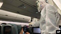 A worker in a hazardous materials suit takes the temperature of a passenger on a Cathay Pacific flight from Hong Kong to Rome after it landed at Rome Fiumicino Airport in Rome, Italy, Friday, Jan. 31, 2020. The U.S. advised against all travel to…