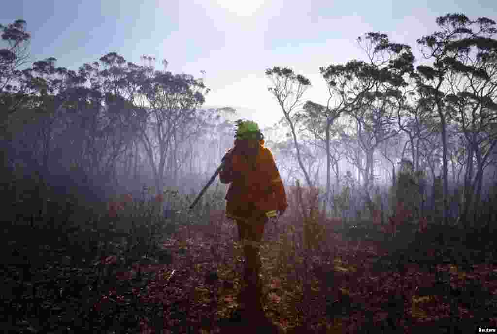 A female Rural Fire Service firefighter walks through a burnt area after trying to extinguish a small fire approaching homes near the Blue Mountains suburb of Blackheath, west of Sydney, Oct. 23, 2013.