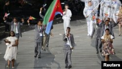 Eritrea's flag bearer Weynay Ghebresilasie holds the national flag as he leads the contingent in the athletes parade during the opening ceremony of the London 2012 Olympic Games, July 27, 2012.