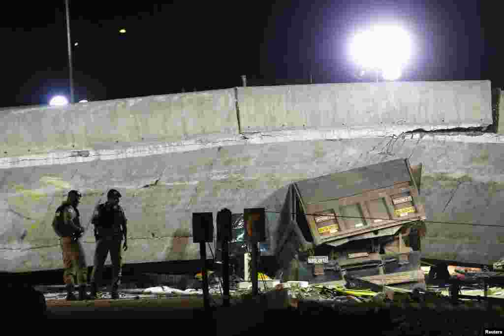 A vehicle is trapped underneath a bridge that collapsed while under construction in Belo Horizonte, July 3, 2014.