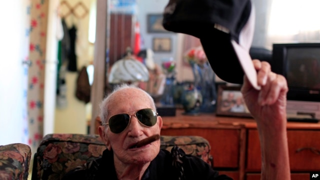 Conrado Marrero, the world's oldest living former major league baseball player, poses for a photo as he holds his baseball cap and an unlit cigar in his mouth two days before his 102nd birthday, at his home in Havana, Cuba, April 23, 2013.