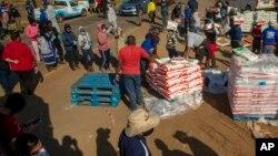 Des personnes touchées par le ralentissement économique du au coronavirus reçoivent des dons de nourriture dans le quartier d'Iterileng près de Laudium, au sud-ouest de Pretoria, Afrique du Sud, le 20 mai 2020.