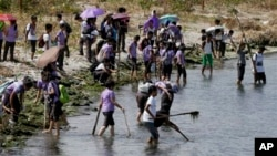 FILE- Students join other environmental activists in a coastal clean-up along the shores of Freedom Island to mark World Earth Day, April 22, 2015 at suburban Las Pinas, south of Manila, Philippines.