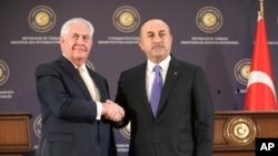 Menteri Luar Negeri Turki Mevlut Cavusoglu, kanan, berjabat tangan dengan Menteri Luar Negeri AS Rex Tillerson, kiri, setelah konferensi pers gabungan setelah pertemuan mereka di Ankara, Turki, 16 Februari 2018.