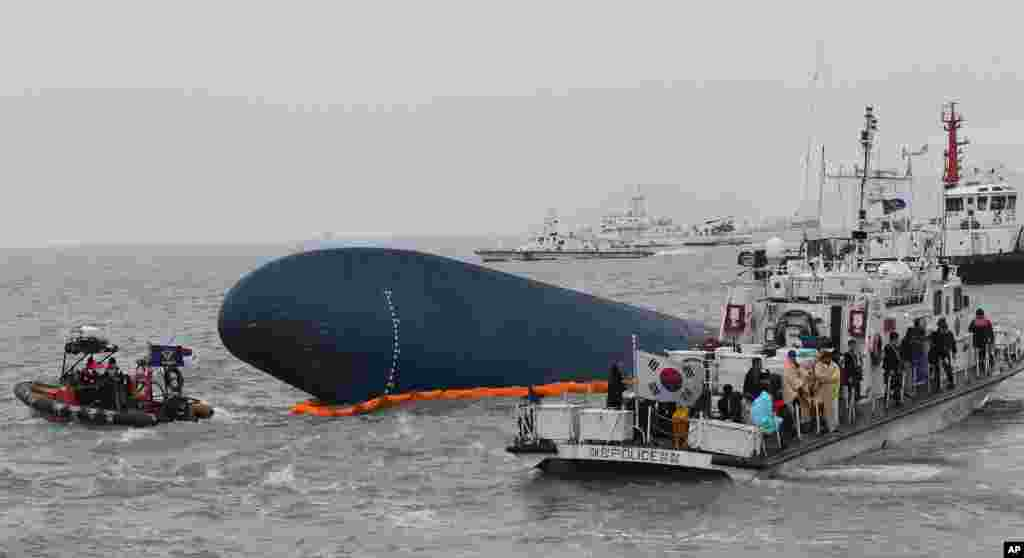 South Korean Coast Guard officers try to rescue missing passengers from a sunken ferry in the water off the southern coast near Jindo, South Korea, April 17, 2014.