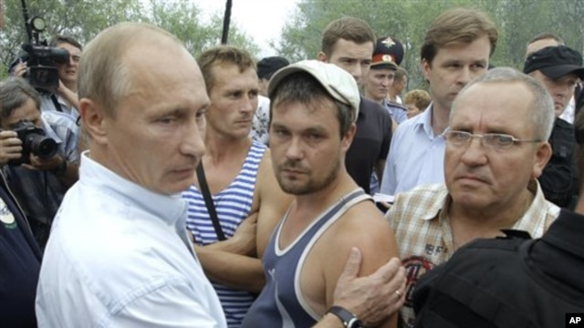 Russian PM Vladimir Putin (l) meets with people, who suffered from forests fires which swept the area in the village of Verkhnyaya Vereya, 30 Jul 2010