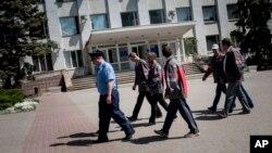 Украинский милиционер с рабочими компании Metinvest патрулируют улицы Мариуполя.16 мая 2014г.