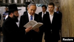 FILE PHOTO: Israel's Prime Minister Benjamin Netanyahu (C) reads a prayer with Western Wall Rabbi Shmuel Rabinowitz (L) as his son Yair (R) stands next to him, at the Western Wall, Judaism's holiest prayer site, in Jerusalem's Old City March 18, 2015.