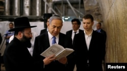 FILE - Israel's Prime Minister Benjamin Netanyahu (C) reads a prayer with Western Wall Rabbi Shmuel Rabinowitz (L) as his son Yair (R) stands next to him, at the Western Wall, Judaism's holiest prayer site, in Jerusalem's Old City.