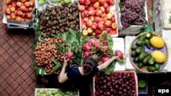 Một phụ nữa bán hoa quả ngoài chợ ở Hà Nội. Ngân hàng Phát triển châu Á dự báo kinh tế Việt Nam sẽ giảm mạnh trong năm nay vì ảnh hưởng sâu của dịch viêm phổi cấp COVID-19.