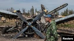 Phiến quân thân Nga đi ngang qua xác một chiếc máy bay bị phá hủy tại phi trường ở Luhanks, miền đông Ukraine, ngày 14/9/2014.