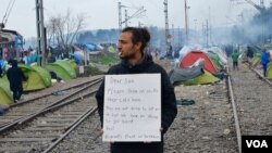 Unidentified man shares message of collective despair taking hold at makeshift refugee camp along Greek-Macedonian border, in Idomeni, Greece, March 16, 2016. (J. Dettmer/VOA)
