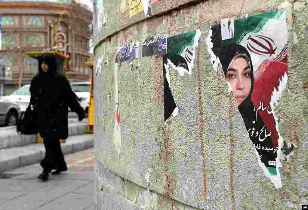 An Iranian woman walks past a torn electoral poster for a parliamentary candidate a day after the elections in Tehran, March 3, 2012. (AFP)