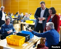 FILE - Andrea Nahles, right, and Lars Klingbeil of Social Democratic Party look on as party members count ballot papers of the voting for a possible coalition between the SPD and the Christian Democratic Union (CDU) in the SPD headquarters in Berlin, Germany, March 3, 2018.