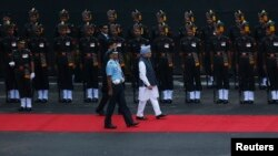 India's Prime Minister Manmohan Singh (C, in blue turban) inspects a guard of honour upon his arrival at the historic Red Fort during Independence Day celebrations in Delhi, August 15, 2013.